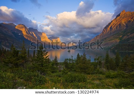 Goose Island Sunrise-- Clearing storm clouds reveal the mountain peaks of Glacier National Park. - stock photo