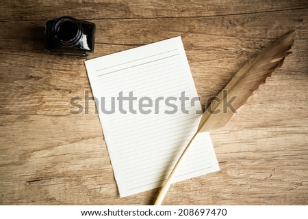 goose quill on empty paper and inkpot on wooden table, retro stylish workplace - stock photo