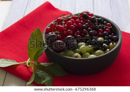 Gooseberries and red currants in a wooden bowl. Ripe and fresh berries. Summer time.