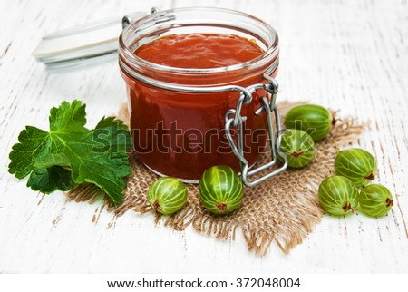 gooseberry jam with fresh berries on a wooden background