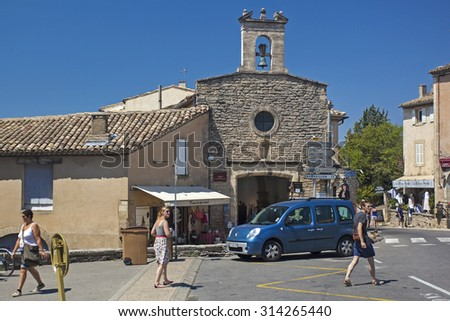 GORDES, FRANCE - AUGUST 12, 2015: People walking on street with White chapel in background.