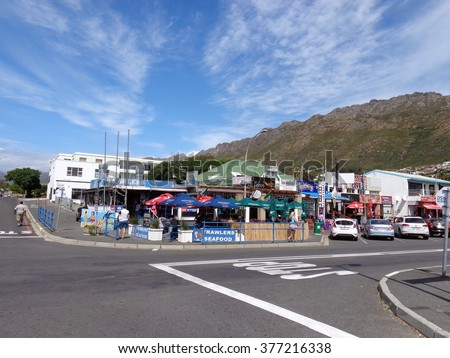 GORDON'S BAY, SOUTH AFRICA - DECEMBER 28, 2013: Strip of beachfront shops and restaurants in the small holiday town near Cape Town, with mountains rising up in the background