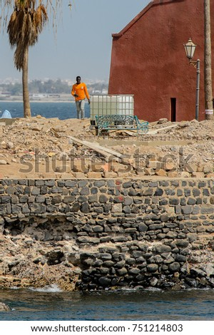 GOREE, SENEGAL - APR 28, 2017: Unidentified Senegalese man walks along the beach in the morning on the Goree Island, the former slave isle