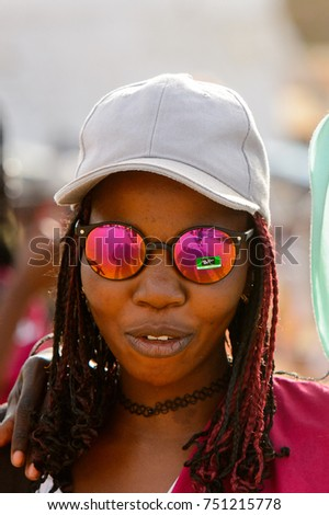 GOREE, SENEGAL - APR 28, 2017: Unidentified Senegalese woman in white cap and sunglasses smiles on the Goree Island, the former slave isle