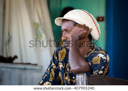 GOREE/SENEGAL - NOVEMBER 11, 2013: Senegalese rasta man with big white hat sitting, looking into the distance and thinking at Goree island, Dakar, Senegal. - stock photo