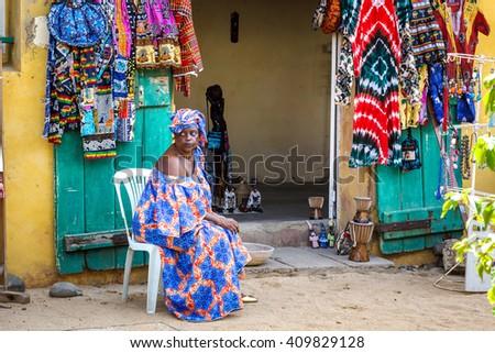 GOREE/SENEGAL - NOVEMBER 11, 2013: Unidentified senegalese women sells colorful african clothes on the street of Goree island, Dakar, Senegal - stock photo