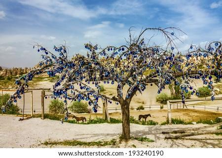Goreme landscape, Cappadocia, Turkey. Tree with popular Turkish souvenir. Traditional blue evil eyes - stock photo