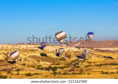 GOREME - OCTOBER 10: Colorful hot air balloons flying  over rock landscape and landing on valleys in Cappadocia on October 10, 2013 in Goreme, Turkey. - stock photo