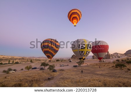 GOREME - OCTOBER 11: Colorful hot air balloons flying over rock landscape at Cappadocia on October 11, 2013 in Goreme, Turkey.  - stock photo