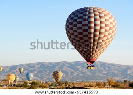Goreme, Turkey - October 16, 2016: Hot air balloons landing after flight over valley of Cappadocia in the morning. Nevsehir Province. Turkey.
