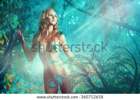 Gorgeous adult sexy woman with butterflies in the jungle - stock photo