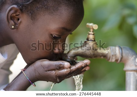 Gorgeous African Black Girl Drinking with Hands Cupped (Drought Symbol)  Young African girl drinking clean water from a tap. Water pouring from a tap in the streets of the African city Bamako, Mali. - stock photo