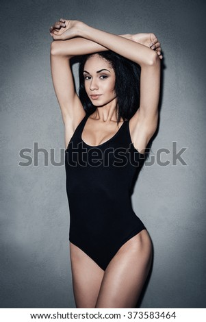 Gorgeous and beautiful. Beautiful young African woman in black swimsuit posing and looking at camera while standing against grey background - stock photo