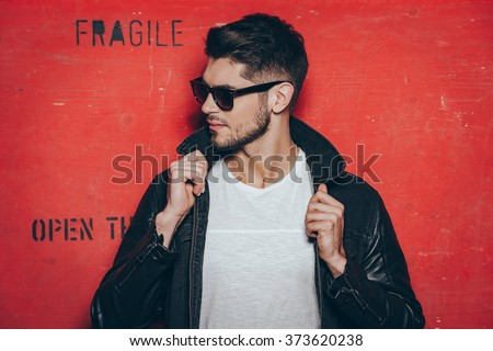 Gorgeous and handsome. Handsome young man in sunglasses adjusting his jacket and looking away while standing against red background - stock photo