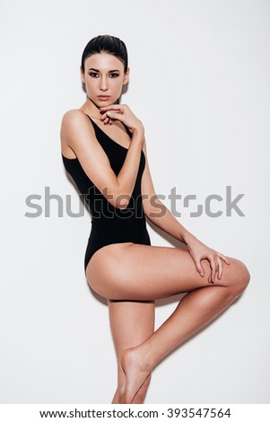 Gorgeous and stylish. Beautiful young woman in black swimsuit posing and looking at camera while standing against white background - stock photo