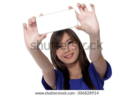 Gorgeous Asian teenage girl smile and take a photo using front camera in her smartphone, isolated on white background. - stock photo