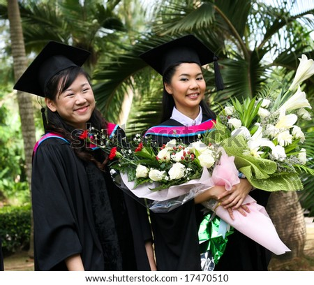 Gorgeous Asian university graduates celebrating their success. - stock photo