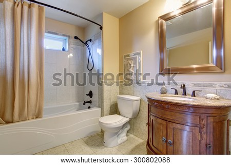 Gorgeous bathroom with tan shower curtain, and gold framed mirror. - stock photo