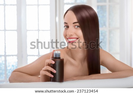 Gorgeous beautiful caucasian female model with perfect hair holding bottle  with shampoo on towel in spa salon with windows on background - stock photo