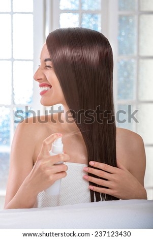 Gorgeous beautiful caucasian female model with perfect hair using hair spray on towel in spa salon with windows on background - stock photo