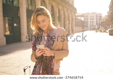 gorgeous beautiful young woman with blonde hair messaging on the smart-phone at the city street background. pretty girl having smart phone conversation in sun flare.  - stock photo