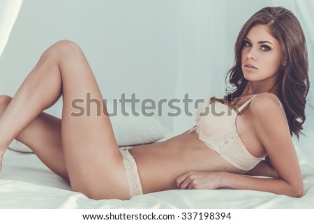 Gorgeous beauty. Beautiful young brown hair woman in lingerie lying in bed and looking at camera - stock photo