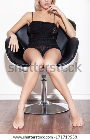 Gorgeous beauty. Cropped image of gorgeous young blond hair woman in lingerie sitting in chair - stock photo