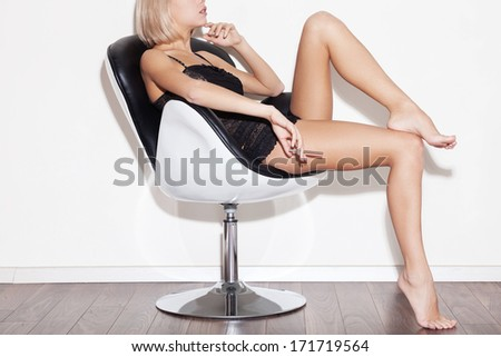 Gorgeous beauty in chair. Side view cropped image of gorgeous young blond hair woman in lingerie sitting in chair and holding cigarette - stock photo