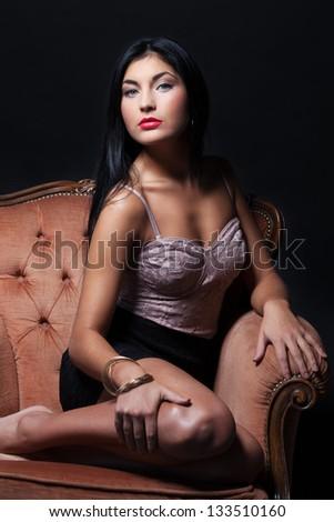 Gorgeous beauty on a luxury armchair - stock photo