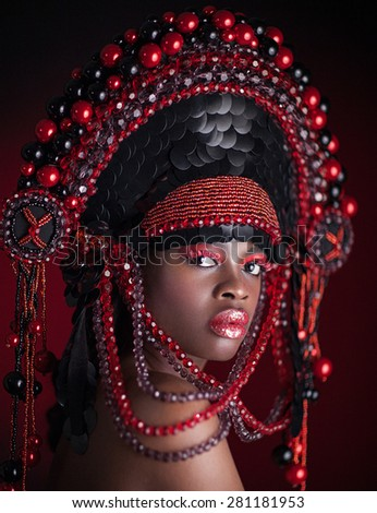 Gorgeous black ethnicity woman with a big magic hat on the head. Unique makeup, red eye shadow and red lipstick.