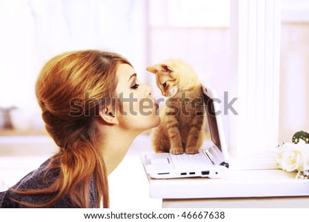Gorgeous blond fashion model kissing a little cat's nose staying on a laptop notebook inside a beautiful home in the chicken
