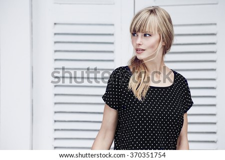 Gorgeous blond in black spotted dress, looking away - stock photo