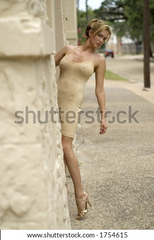 gorgeous blond on the street leaning around a building