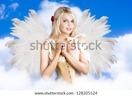 Gorgeous Blond Woman Flying Above A Heavenly Cloud With Soft Fairy Wings While Clasping Heart In A Depiction Of Cupid The Angel Of Love
