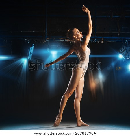 Gorgeous blonde ballerina posing on theater stage against spotlights - stock photo