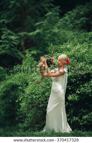 Gorgeous blonde bride in elegant dress holding bouquet and posing in the sunny summer park or garden on their wedding day