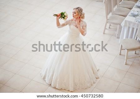 Gorgeous blonde bride posed indoor great wedding hall - stock photo