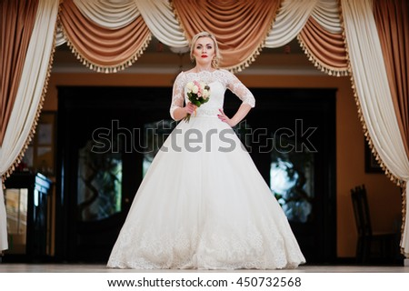 Gorgeous blonde bride posed indoor great wedding hall background curtains - stock photo