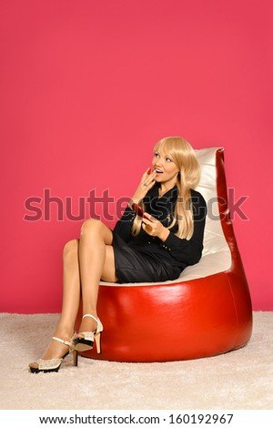 Gorgeous blonde businesswoman putting makeup on red background