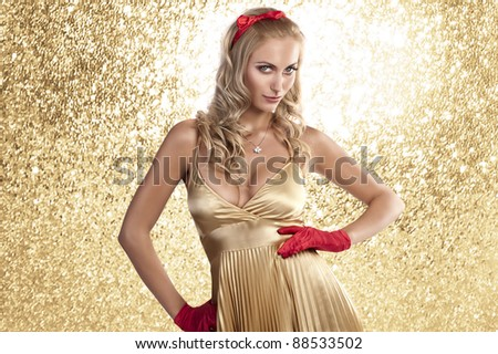gorgeous blonde girl in a golden dress and red hair bow and red gloves posing for christmas - stock photo
