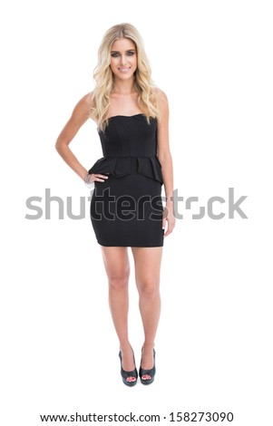 Gorgeous blonde girl in classy black dress posing on white background - stock photo