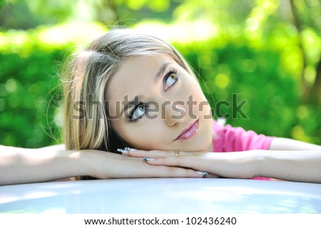 Gorgeous blonde girl leaning against a car and looking up outdoors - stock photo