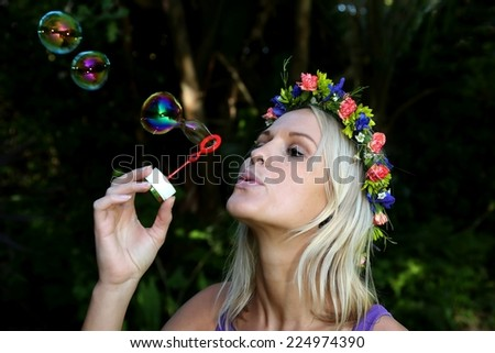 Gorgeous blonde girl with flower garland blowing bubbles outdoors - stock photo
