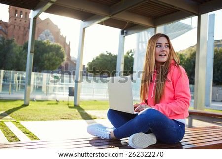 Gorgeous blonde hair female student looking away for someone while busy using laptop computer at campus,charming female teenager sitting on park bench with open laptop at spring sunny day - stock photo