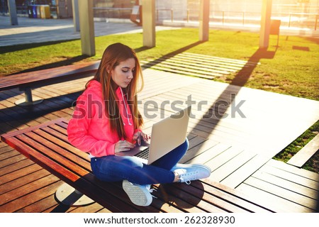 Gorgeous blonde hair female student typing on laptop keyboard sitting at campus, charming female teenager studying for exam on park bench with open net-book and big copy space for text, flare sunshine - stock photo