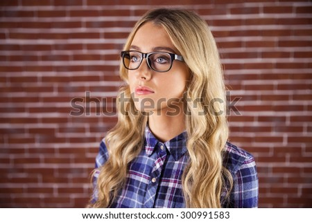 Gorgeous blonde hipster being serious against red brick background