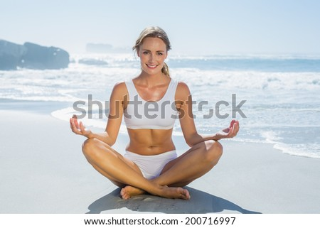 Gorgeous blonde in lotus pose by the sea on a sunny day
