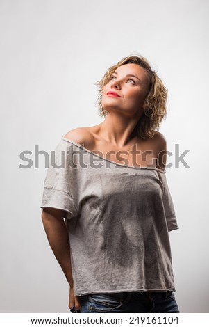 Gorgeous blonde posing in the studio. Beautiful blonde in casual clothes. Beautiful eye makeup, lips, correct skin tone. - stock photo