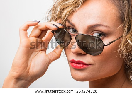 Gorgeous blonde posing in the studio. Beautiful blonde in sunglasses. Beautiful eye makeup, lips, correct skin tone. - stock photo