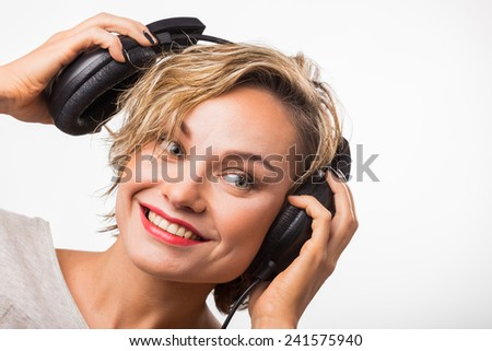 Gorgeous blonde posing on light background. Beauty, fashion photography. Girl in stereo headphones. Young blond woman listening to music on headphones.  - stock photo
